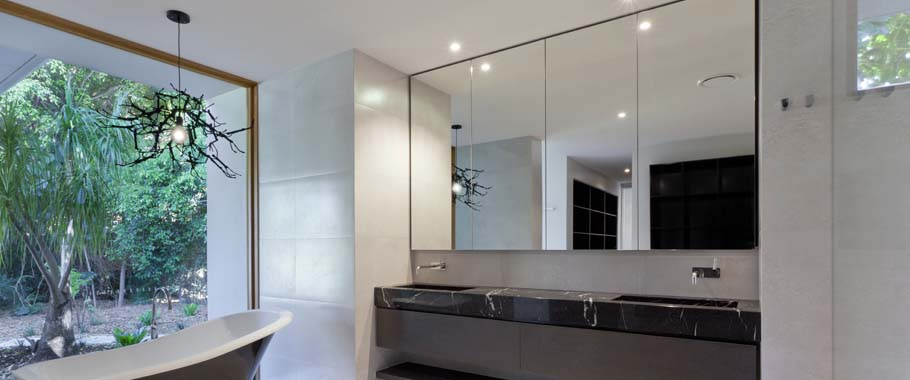 Mirror above sink in bathroom with glass wall